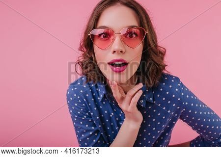 Good-humoured Female Model With Brown Curly Hair Posing In Funny Sunglasses. Indoor Photo Of Pleased