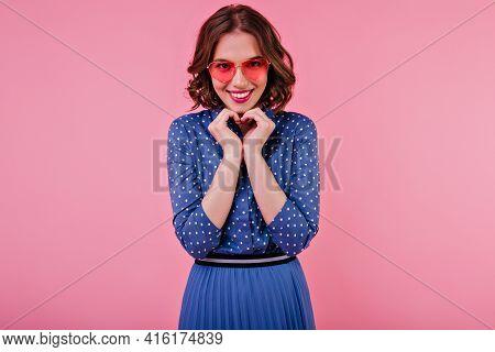 Romantic Brunette Lady In Elegant Blue Attire Posing In Studio With Smile. Indoor Shot Of Beautiful