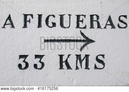 Directional Roadsign To Figueras Located At 33 Km Painted On White Wall With Black Arrow. Catalonia,