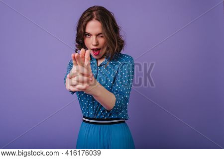 Short-haired Playful Woman In Trendy Attire Posing On Purple Background. Good-humoured Female Model