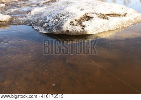 Dirty Puddle Of Melted Snow. A Small Melting Snowdrift.