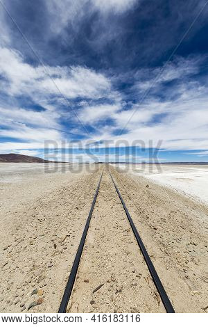 Railway With The Desert, Blue Sky And The Mountains In The Background In Atacama Desert, Uyuni Deser
