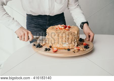 The Pastry Chef Is Cutting The Cake. A Delicious Honey Cake Is Cut With A Knife. Close-up Of Honey C