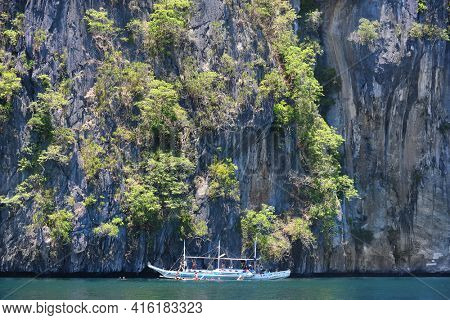 EL NIDO, PALAWAN, PHILIPPINES - APRIL 5, 2016:  Pleasure boat with tourists swimming in the waters off of El Nido Island in the Philippines.