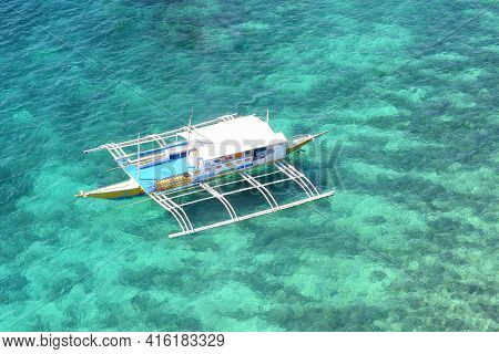 BOHOL, PHILIPPINES - APRIL 5, 2016:  Outrigger anchored in the blue-green tropical waters off the coast of Bohol in the Philippines.