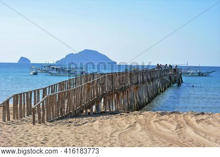 EL NIDO, PALAWAN, PHILIPPINES - APRIL 5, 2016:  Wooden boat dock at the El Nido airport. Travelers leave the airport and board boats to other island destinations.El Nido Boat Dock