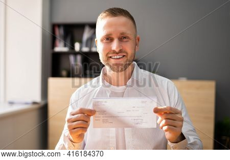 Holding Paycheck In Hand. Insurance And Payroll Check