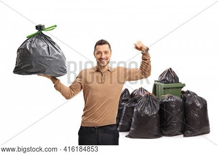 Young man holding a garbage bag and flexing his biceps in front of a dustbin isolated on white background
