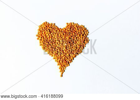 Raw red lentils seeds heap in heart shape on white background. Food ingredient. Top view.