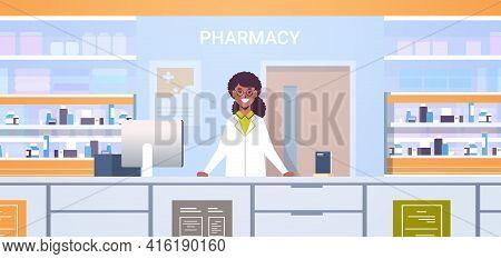 African American Female Doctor Pharmacist Standing At Pharmacy Counter Modern Drugstore Interior Med