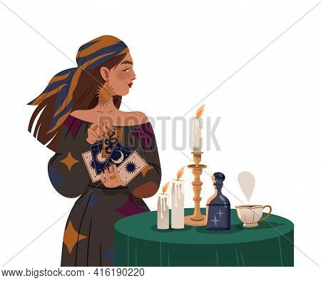Gypsy Woman As Fortune Teller Holding Tarot Cards At Table With Candle Predicting Future Or Performi