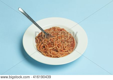 Spaghetti Pasta With Tomato Sauce On A White Plate On A Blue Empty Background. Italian Pasta Dish Ba