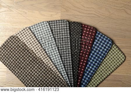 Types And Samples Of Carpets In Different Colors On Wooden Floor Backgrond. Carpets For Rooms, Apart