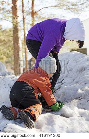 Umea, Norrland Sweden - March 17, 2021: Big Brother Helps Little Brother Up On A Snowdrift