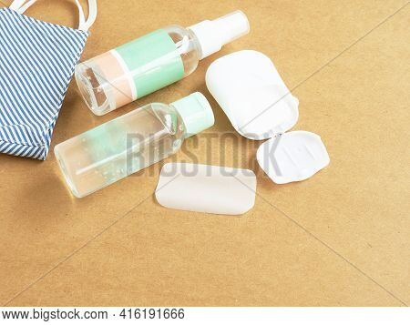 Alcohol Gel, Spray And Portable Soap Sheet With Blue Fabric Face Mask On A Brown Background, Used Fo