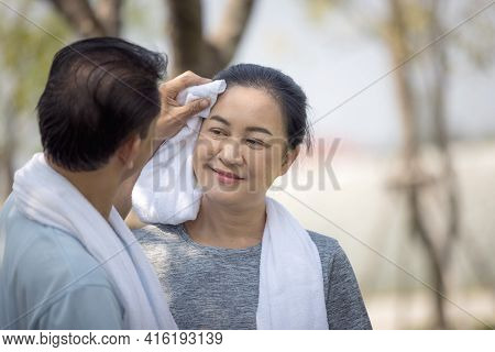 Asian Happy Senior Couple Husband Wiping Sweat From Wife's Face After Running At The Outdoor Park.
