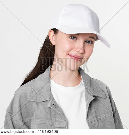 Teenage girl in stylish outfit and white cap studio portrait for youth apparel shoot
