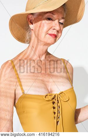 Senior woman in yellow one-piece swimsuit summer apparel