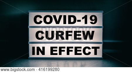 Curfew in effect text message on lit lightbox for covid coronavirus pandemic. Warning at night.