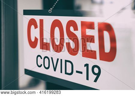 COVID Closed Sign hanging in window storefront. Government mandatory shutdown order of restaurants, non essential stores or curfew forcing closure of businesses leading to unemployment. Coronavirus.
