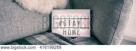 Stay home prevention message on white sign at home indoors. Coronavirus text asking people staying home for social distancing. Panoramic banner billboard on sofa.
