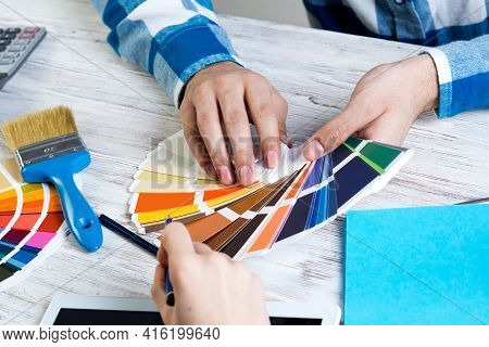 Interior Designer Choosing Colors From Swatches At Wooden Desk. Office Workplace In Design Studio. S