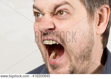 An Angry Aggressive Man Screams With Mouth Open. A Human Cry At A Child Or A Quarrel In The Family.