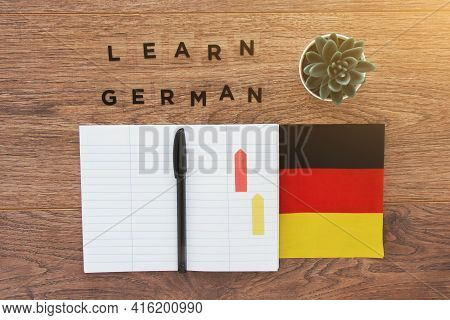 German Flag, Notebook, Pen And Inscription Learn German On A Wooden Desktop, Foreign Language Learni