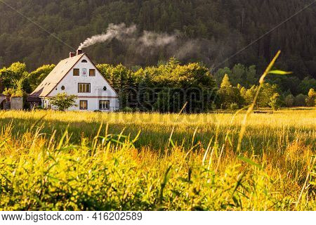 Rural View, A Traditional Polish Country Cottage House With Smoke From The Chimney Next To Pine Fore
