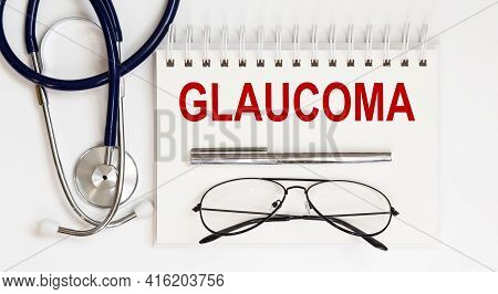 Stethoscope,glasses And Pen With Notepad With Text A Glaucoma On White Background