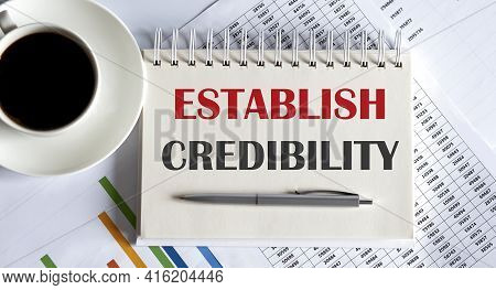 Text Establish Credibility On Notepad With Office Tools, Pen On Financial Report