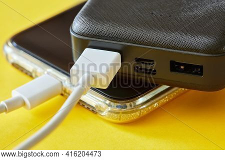 Power Bank Charges Smartphone Using A Usb Cable On Yellow Background. Close-up, Selective Focus