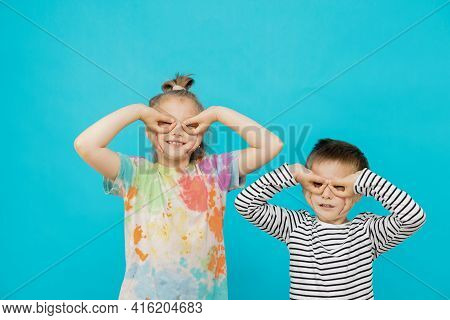 Cute Caucasian Children, A Girl And A Boy Make Aviator Glasses From Hands On A Blue Background With