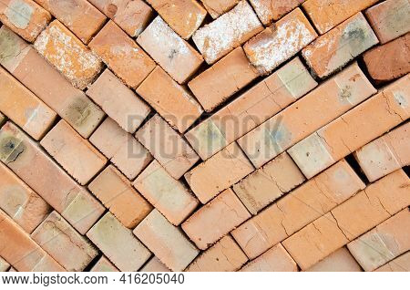 Close Up Texture Of Piled Bricks. Background From Red Bricks Stacked On Top Of Each Other. Construct