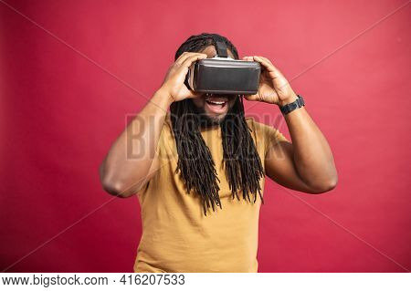 Black Happy Man With Long Dreadlocks Dressed In Casual Clothes, Standing Isolated Over Red Backgroun