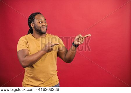 Positive Black African American Unshaved Man With Dreadlocks Looks And Points To The Side With Both