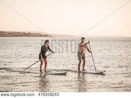 Mature Couple On Sup, Stand Up Paddle Board, Having Fun On Quiet Sea At Sunset