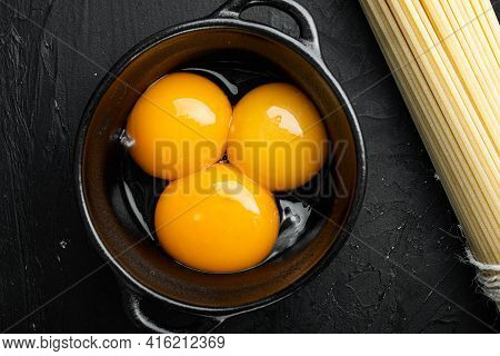 Bright Yellow Egg Yolks Set, On Black Stone Background, Top View Flat Lay
