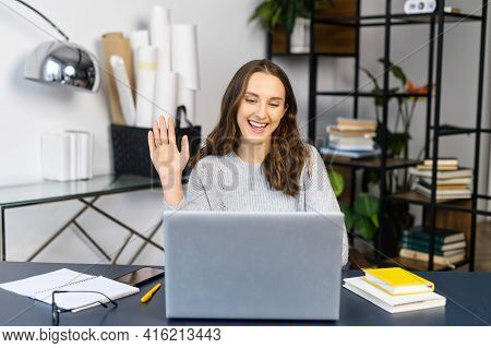 Video Meeting Concept. Cheerful Young Woman Has Video Call On The Laptop At Office, Waving Hi Into W