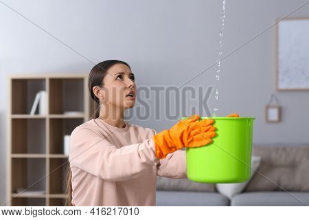 Young Woman Collecting Leaking Water From Ceiling At Home. Time To Call Roof Repair Service