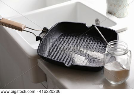 Dirty Grill Pan And Jar With Baking Soda On Countertop Near Sink In Kitchen