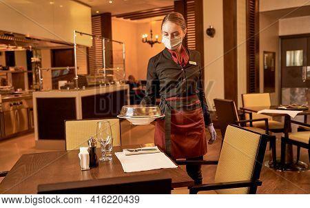Female Server Bringing A Dish Under A Steel Lid