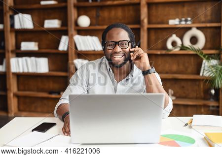Cheerful African-american Male Employee Wearing Headset Adjusts The Microphone, Holding A Call, Talk