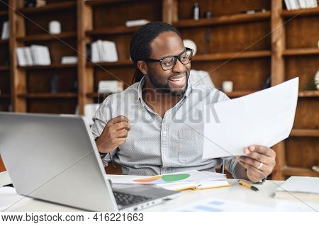 Happy African-american Businessman In Eyeglasses Looks At A Document, Satisfied With Report Results,