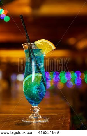 Blue Non-alcoholic Cocktail With Lemon Decorated With An Orange Slice On The Bar. Close-up, Selectiv