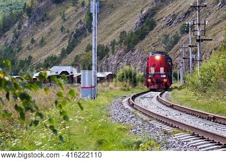 Red Vintage Train Running By Railway At The Foot Of A Mountain. Summer Travel Concept.