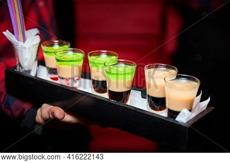The Waiter Holds A Tray With Multicolored Alcoholic Shots. Close-up, Selective Focus
