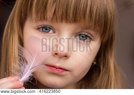 Close-up Portrait Of A Little Girl And A Feather Of A Bird In Her Hands Stroking Her Cheek, Gentle T