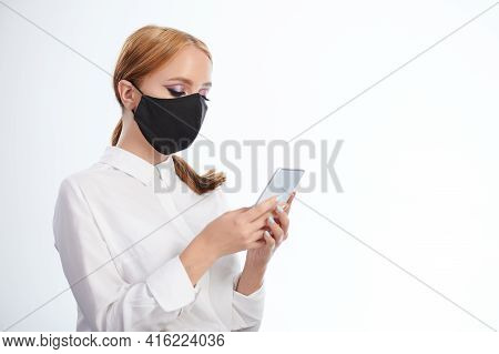 Woman Send Message Via Smartphone In Mask Isolated On Studio Background