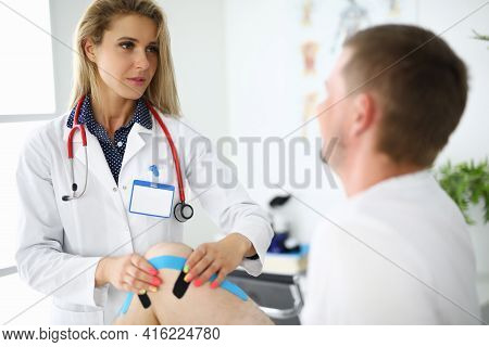 Doctor Physiotherapist Sticking Tapes On Man Sore Knee